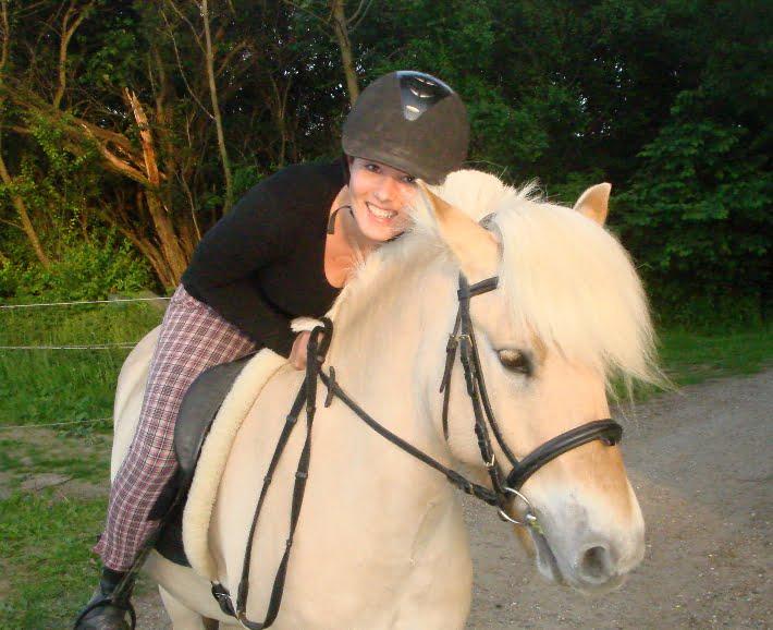 Gitte sidder på ryggen af sin hest og smiler